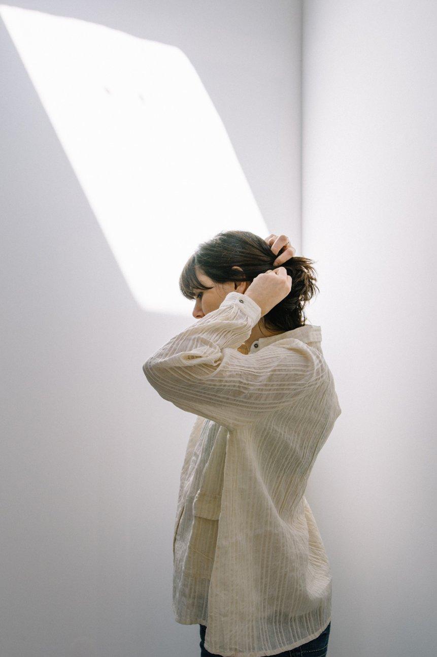 mujer de espaldas recogiéndose el pelo