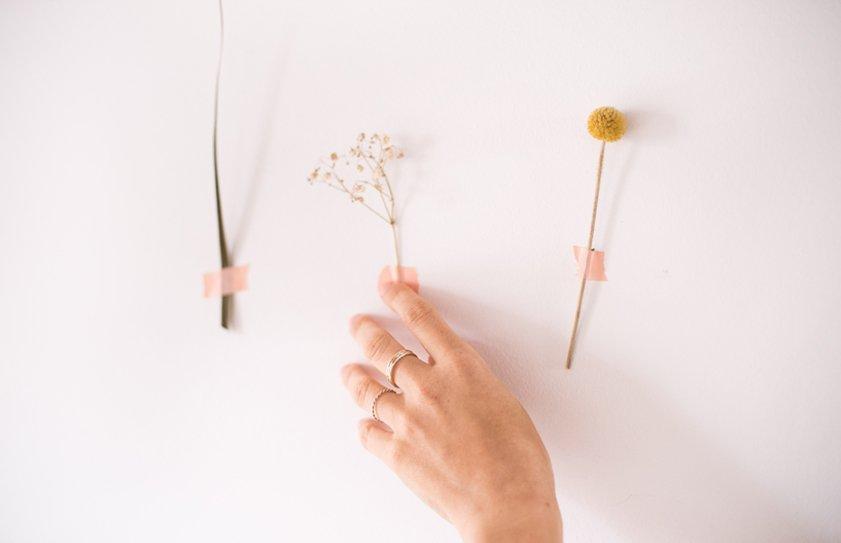 mano sobre flores en pared
