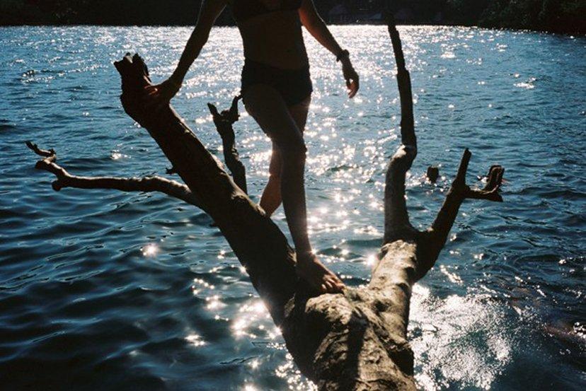 chica sobre tronco en el mar