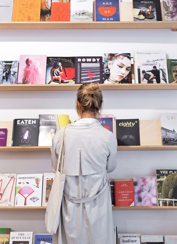 chica frente a pared con revistas